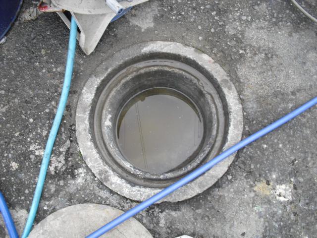 排水桝の中に水が溜まっているパイプ詰まりを高圧洗浄で除去